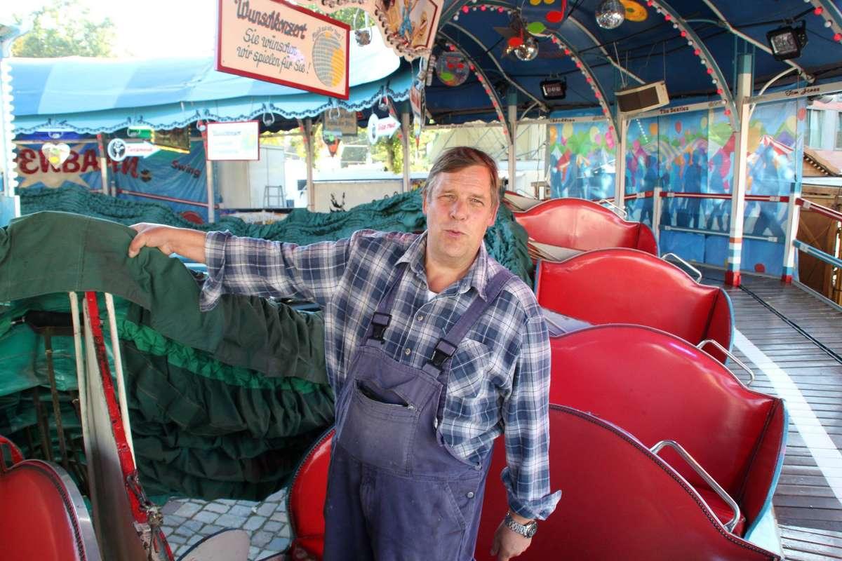 """Ein """"Knutschkarussell"""": Peter Buchholz steht an seiner """"Raupenbahn"""" und zieht an der Stoffdecke, die sich zum Fahrtende über die Gondeln legt."""